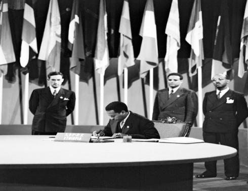 ምክትል የሕግ ሚኒስትርና የኢትዮጵያ ልዑካን አባል አቶ አምባዬ ተወልደማርያም በኢትዮጵያ መንግሥትና ሕዝብ ስም የተባበሩት መንግሥታትን ቻርተር ሳንፍራንሲስኮ ላይ እ.ኤ.አ. ሰኔ 26፣ 1945 ዓ.ም. ሲፈርሙ UN (Photo courtesy: /McCreary)