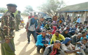 GARISSA (Xinhua) -- Kenyan police officers guard the arrested Ethiopian immigrants in Garissa, northeastern Kenya, Sept. 22, 2014. Kenyan authorities arrested on Monday some 105 Ethiopian immigrants who had sneaked into the country through the porous border in Moyale, northern region. XINHUA PHOTO: STEPHEN INGATI