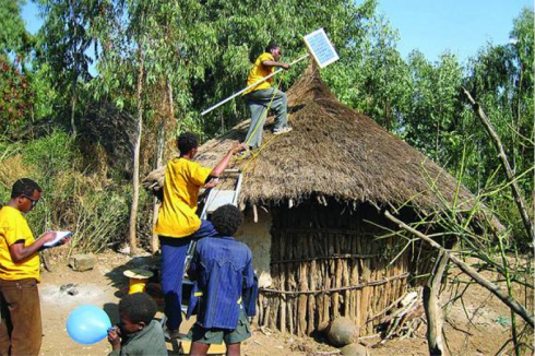Ethiopian youth put solar panel for energy to a collapsing home as the owners watch; hope the way down would not deprive the owners their abode  (foto: Addis Fortune)